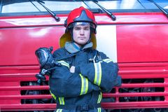Portrait of a fireman. With car on background Stock Photos