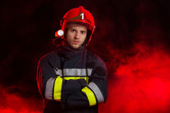 Portrait of the fireman. Serious fireman in red helmet standing with arms crossed. Waist up studio shot on black background and red smoke Royalty Free Stock Image