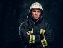 Brutal fireman in uniform posing for the camera standing with crossed arms and confident look. stock photos