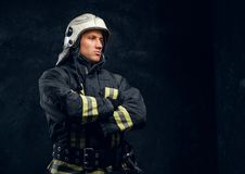 Portrait of a fireman in uniform and helmet stands with crossed hands, looking sideways with a confident look. royalty free stock photography