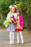 Portrait first grader and her younger sister on way to school. Portrait first grader and her younger sister on the way to school royalty free stock photography
