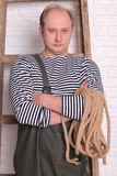 Portrait of a fisherman in waders with rope. On the white wall background Stock Images