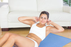 Portrait of fit calm woman doing sit ups on exercise mat Stock Photography