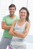 Portrait of a fit couple with arms crossed in exercise room Royalty Free Stock Photography