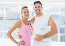 Portrait of a fit couple holding weighing scale Royalty Free Stock Photos