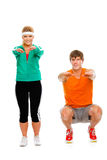 Portrait of fit girl and man sitting on squat Stock Photo