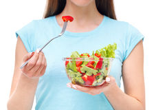 Portrait of a fit healthy woman eating a fresh salad isolated. On white background Stock Photo
