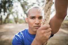Portrait of fit man climbing rope during obstacle course. In boot camp royalty free stock images