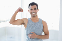 Portrait of a fit man flexing muscles in fitness studio Royalty Free Stock Image