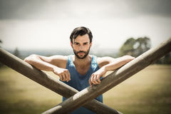 Portrait of fit man leaning on wooden bar during obstacle course Royalty Free Stock Photo