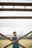 Portrait of fit man leaning on wooden bar during obstacle course Stock Photos
