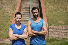Portrait of fit man and woman standing with arms crossed against staircase. Portrait of fit men and women standing with arms crossed against staircase in boot royalty free stock photos