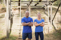 Portrait of fit man and woman standing with arms crossed. Portrait of fit men and women standing with arms crossed in boot camp stock images