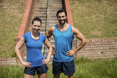 Portrait of fit man and woman standing with hands on hip against staircase Stock Photo