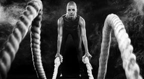 Battle ropes session. Attractive young fit and toned sportswoman working out in functional training gym doing exercise stock photo