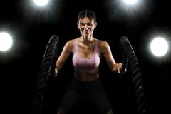 Battle ropes. Fit sports woman, athlete working out in functional training doing exercise on black background. Fitness royalty free stock photography