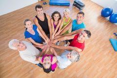 Portrait of fit people stacking hands. High angle portrait of fit people stacking hands at health club Royalty Free Stock Photography