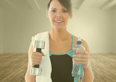 Portrait of fit woman holding dumbbell and water bottle Stock Image
