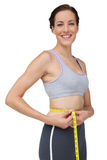 Portrait of a fit woman measuring waist Royalty Free Stock Image