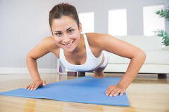 Portrait of fit woman practicing press ups in her living room Royalty Free Stock Images