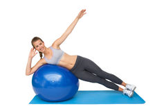 Portrait of a fit woman stretching on fitness ball Royalty Free Stock Photo