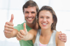 Portrait of a fit young couple gesturing thumbs up Stock Photos