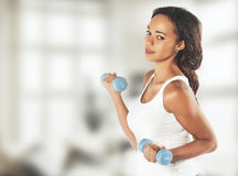 Portrait of a  fit young lady working out with dumbbells. Vintag Stock Photography