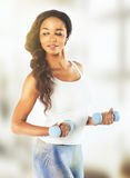 Portrait of a  fit young lady working out with dumbbells. Vintag Stock Photos