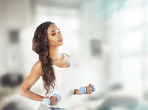 Portrait of a  fit young lady working out with dumbbells. Vintag Stock Images