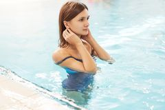 Portrait of a fit young woman. Brunette sexy woman with perfect body posing in fashionable swimsuit, relaxing on pool. royalty free stock images