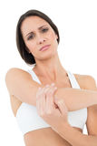Portrait of a fit young woman with elbow pain. Over white background Stock Photography