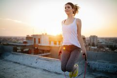 Portrait of fit young woman with jump rope on rooftop. Fitness female doing skipping workout outdoors on a sunny day. royalty free stock photo