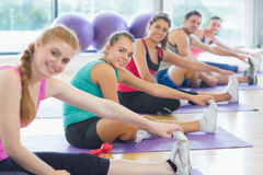 Portrait of fitness class and instructor stretching legs Stock Photos