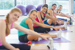 Portrait of fitness class and instructor stretching legs Stock Images