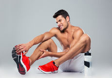 Portrait of a fitness man with foot pain. Over gray background royalty free stock photo
