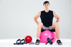 Portrait of a fitness man sitting on the ball Royalty Free Stock Photography