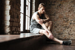 Portrait of a fitness man suffering from a leg pain. Portrait of a young fitness man suffering from a leg pain while sitting on the windowsill at the gym stock images