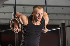Fitness Man Training Arms With Gymnastics Rings. Portrait Of A Fitness Man Training Arms With Gymnastics Rings In The Gym Stock Photos