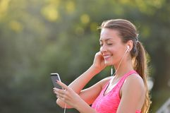 Portrait of fitness woman choosing music on her smartphone Stock Image