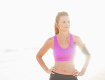 Portrait of fitness woman in headphones outdoors in rays of light Stock Image