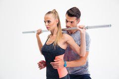 Portrait of a fitness woman lifting barbell with trainer Royalty Free Stock Image