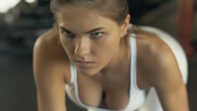 Portrait fitness woman lifting dumbbells for training muscle back in gym club. Close up woman bodybuilder training with weights dumbbells on modern fitness stock footage