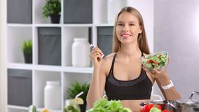 Portrait of fitness woman posing with bowl of fresh appetizing vegetable and fork at kitchen