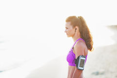 Portrait of fitness young woman in headphones on beach Stock Photography