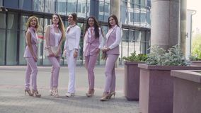 Portrait of five business women outdoors. Portrait of five attractive business women posing near business centre. Summer day. Color grading version black and stock video footage