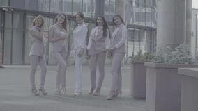 Portrait of five business women outdoors. Portrait of five attractive business women posing near business centre. Summer day. No grading version black and white stock video footage