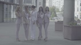 Portrait of five business women outdoors. Portrait of five attractive business women posing near business centre. Summer day. No grading version black and white stock footage