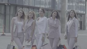 Portrait of five business women outdoors. Portrait of five attractive business women with shopping bags posing near business centre. Summer day. No grading stock footage