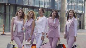 Portrait of five business women outdoors. Portrait of five attractive business women with shopping bags posing near business centre. Summer day. Color grading stock video footage