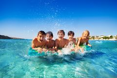 Friends having fun with air mattress in the sea stock photo